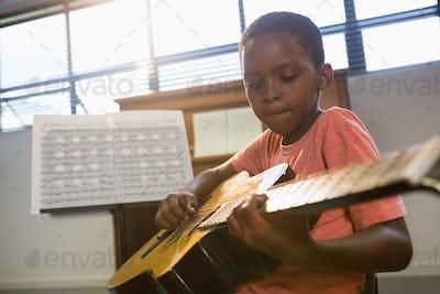 Boy playing guitar in class