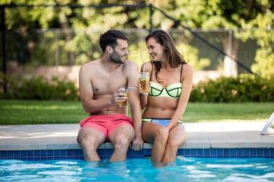 Young couple having iced tea at poolside