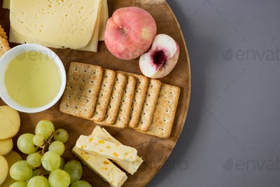 Variety of cheese with grapes, peach and crackers
