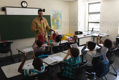 Schoolkids applauding while male Caucasian firefighter teaching about fire safety in classroom