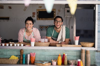 Portrait of waiter and waitress leaning at counter