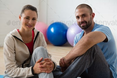 Portrait of student and instructor relaxing in yoga studio
