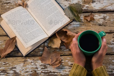 Cropped hand holding coffee cup by book