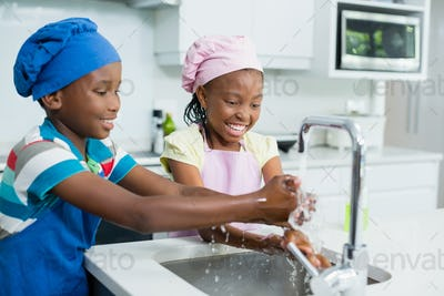 Siblings washing hand in kitchen at home