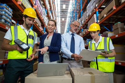 Warehouse manager and client interacting with co-workers