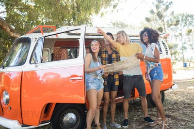Man gesturing away while standing with friends by camper van
