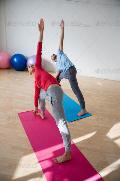Instructor with student practicing triange pose in yoga studio
