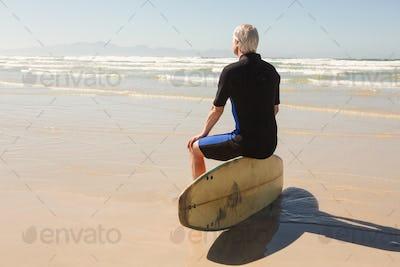 Rear view of senior man sitting on surfboard
