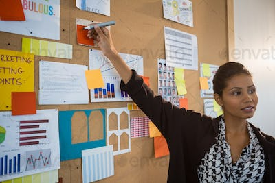 Female executive pointing at sticky note on bulletin board