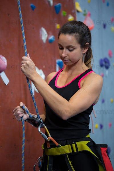 Woman preparing for rock climbing in fitness studio