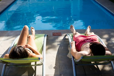 Couple relaxing on lounge chair at poolside