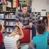 Schoolkids raising their hands while teacher teaching in library
