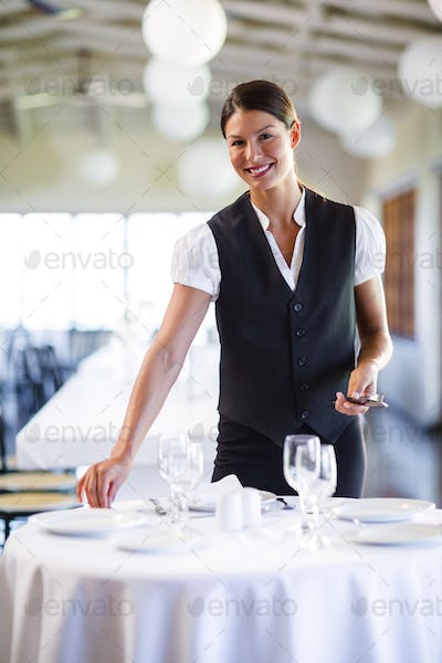 Portrait of smiling waitress setting the table