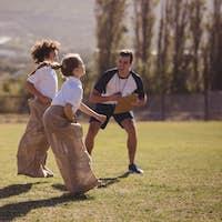 Coach cheering schoolgirls during sack race in park