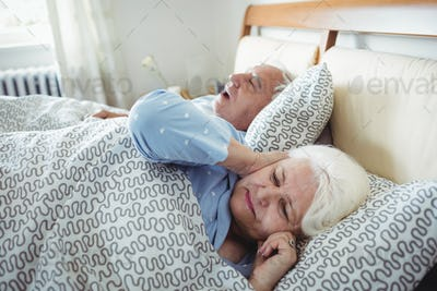 Man snoring and woman covering her ears while sleeping on bed