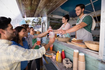 Waitress and waiter giving juice to customer at counter