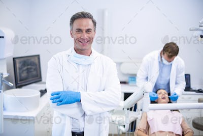 Smiling dentist standing with arms crossed