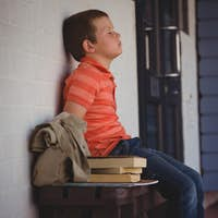 Sad boy with eyes closed sitting on bench by wall in corridor