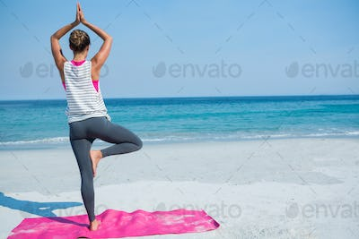 Full length of woman practicing yoga in tree pose at beach