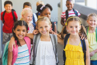 Smiling kids standing with arm around in corridor