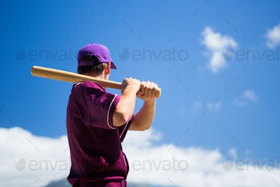 Low angle side view of baseball player holding bat against blue sky