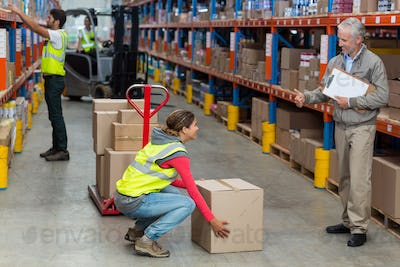 Warehouse manager showing thumbs up to female worker while carrying cardboard boxes