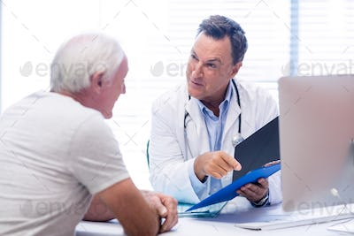 Doctor and senior man discussing on file