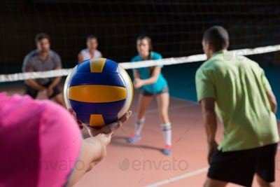 Cropped hand of player with teammates holding volleyball