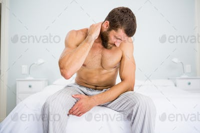 Man suffering from neck ache on bed