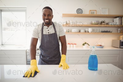 Smiling man cleaning the kitchen worktop