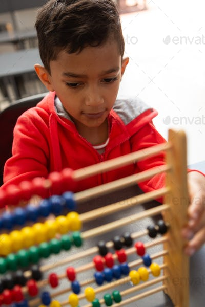 Schoolboy learning math with abacus at desk in a classroom