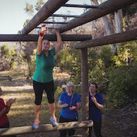 Woman being cheered bye her teammates to climb monkey bars during obstacle course training