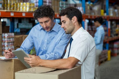 Warehouse workers discussing with digital tablet