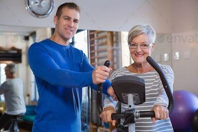 Physiotherapist assisting senior woman on exercise bike