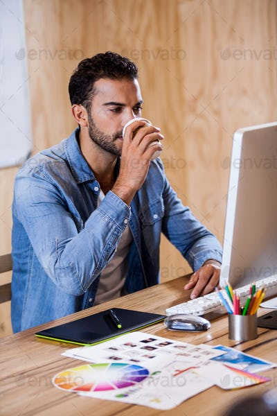 An attractive man working at computer desk