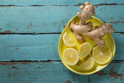 Lemon and ginger in yellow plate on table