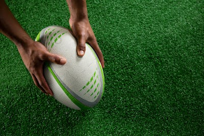 High angle view of hands holding rugby ball