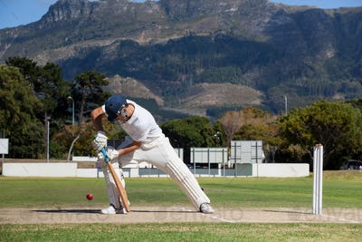 Full length of batsman playing cricket on field against mountain