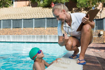 Female trainer showing stopwatch to boy