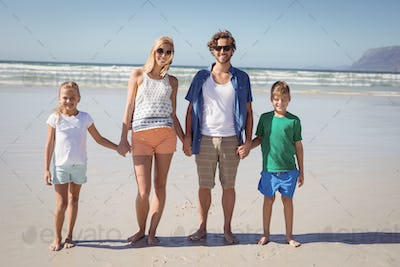 Portrait of family holding hands while standing together at beach