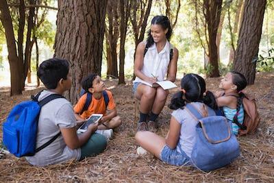 Happy teacher sitting on tree stump amidst children in forest