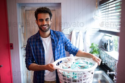 Portrait of smiling young man holding laundry basket