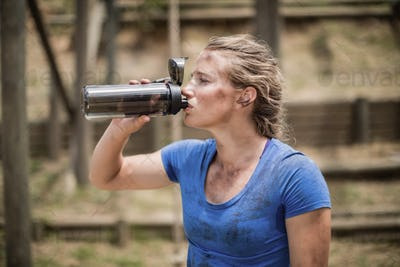 Woman drinking water from bottle during obstacle course