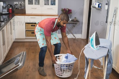 Young man lifting laundry basket by ironing board in kitchen