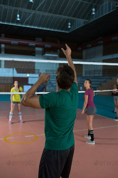 Rear view of player practicing volleyball