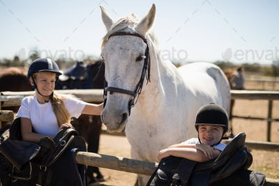 Two girls standing next to the white horse in the ranch