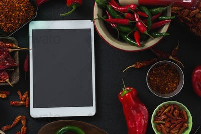 Various spices with digital tablet on black background