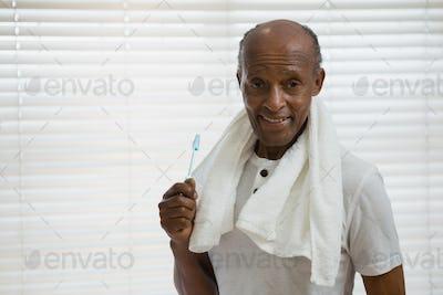 Portrait of senior man holding toothbrush against window