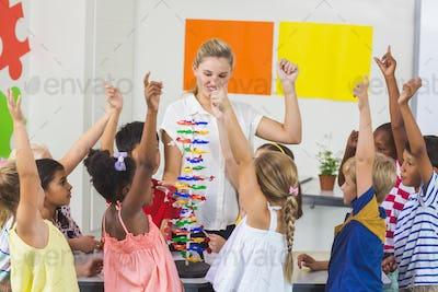 Teacher assisting kids in laboratory