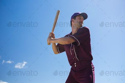 Low angle view of young baseball player holding bat against blue sky